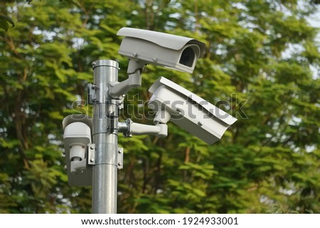 CC.TV. cameras on metal pole in public park for monitor, observe and record evident of incident for investigation and prevent criminal.  Safety, CC.TV. camera concept.