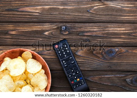 cchips, TV remote control on a wooden table background.  entertainment, leisure, recreation.