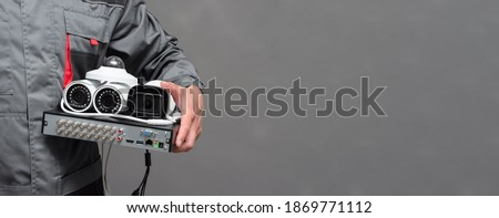 CCTV camera and video surveillance equipment in the worker hands on the gray background with copy space. Foto stock ©
