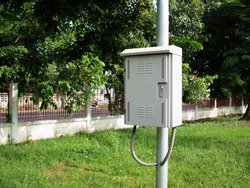 CCTV control box on the pole. A white metal box was mounted on a steel post and below it was conduit. On the background there are lawns, fence lines and green trees with copy space. Selective focus