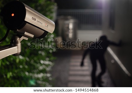 CCTV surveillance camera operate during night capture thief while break into a house Foto stock ©
