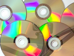 CD and DVD discs as a background. Discs with movies, music, and games. Many iridescent DVDs as an abstract and original background.