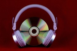 CD and headphones isolated on a red background