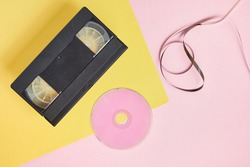 cd disc and videotape on pink and yellow background, vintage video cassette and compact disc with pink label copy space top view