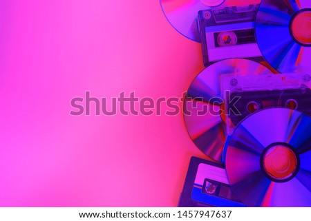 CD disks and audio cassettes on a pink violet purple neon background. Minimalism #1457947637