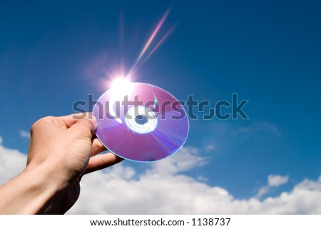 cd in hand, lens flare, blue sky and clouds as background