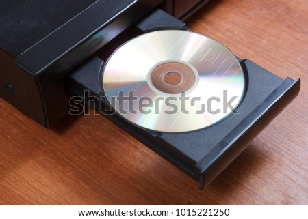 cd in retro cd player opened tray on brown table