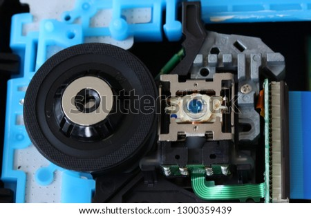 CD inside a DVD payer showing optical pick up laser lens with circuits, cables and boards - close up #1300359439