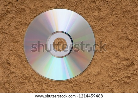 CD is on the sand, CD-ROM is on the ground, disk is on a beach, CD-ROM disk is on textured background, DVD is on the earth, lost music, find inspiration,