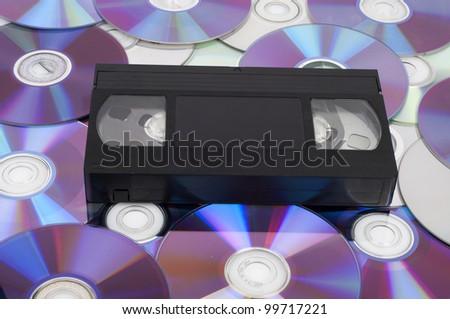 CD vs VHS. VHS cassette lay on the many CD disks