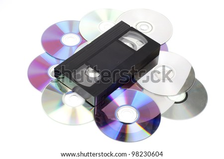 CD vs VHS. VHS cassette lay on the many CD disks isolated on white background