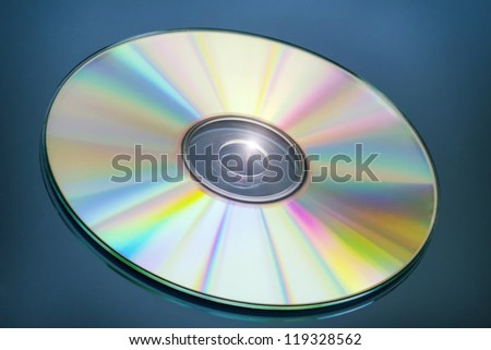 CD with spectrum colors on blue mirror