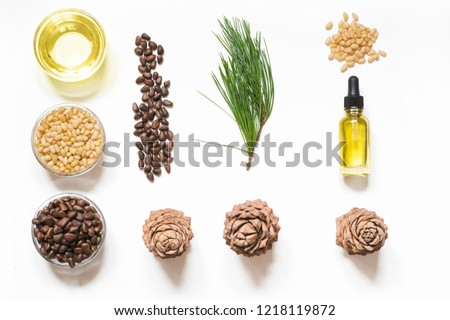 Cedar oil, branches and cedar cone on white background. Copy space. Beauty and healthy concept.