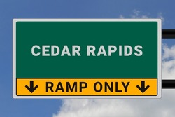 Cedar Rapids logo. Cedar Rapids lettering on a road sign. Signpost at entrance to Cedar Rapids, USA. Green pointer in American style. Road sign in the United States of America. Sky in background