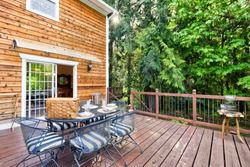 Cedar wooden large American house extrerior with green nature and cozy private deck with metal chairs and table sent up for lunch or picnic.