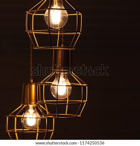 Ceiling chandelier with hanging three bulb lamps, yellow LED lighting elements covered with metal wire frame lampshades, square framed photo with selective focus #1174250536