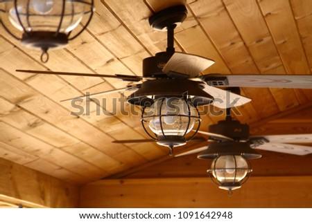Ceiling fan in a wooden cabin #1091642948