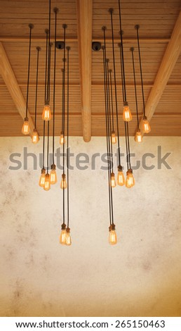 ceiling light bulb hanging on pine wood against warm tone of grungy cement wall use as home decorated background,backdrop and copy space