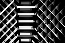 Ceiling or pitched roof structure. Architectural detail. Minimal architecture of modern building in darkness. Abstract material background with parallel lines. Construction industry and technology.