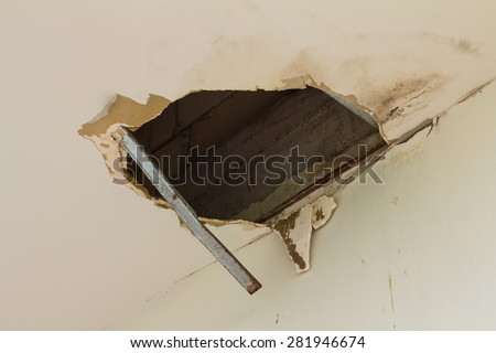 Ceiling panels damaged as a huge hole in the roof from rainwater leakage.