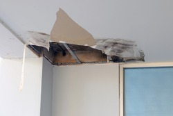 Ceiling panels damaged hole in the roof office from drain pipes water leakage. Office building or house problem from plumber system.