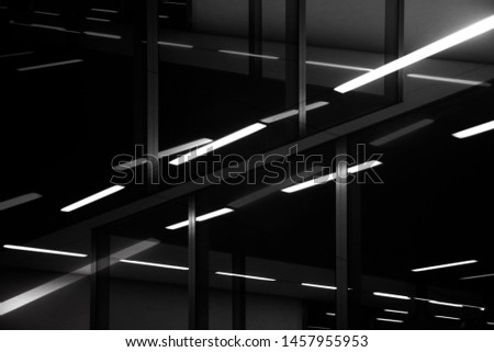 Ceilings with fluorescent lamps in industrial or office building. Grunge abstract black and white background on the subject of modern architecture, construction industry or technology.