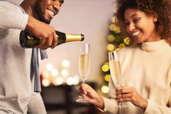 Celebrate Christmas together. Man pouring champagne into glasses