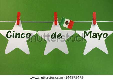 Celebrate Cinco de Mayo holiday on May 5 with Cinco de Mayo message greeting written across white stars and Mexico flag hanging pegs on a line against a green background.