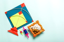 Celebrate Indian festival makar sankranti with colorfull kite,sesame seed ball,tilgul and chakri with background