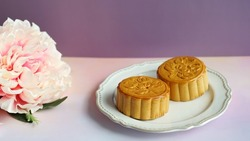 Celebrate Mooncake festival with traditional mooncakes on vintage plate over pastel pink and purple background with blurred peony flower. Holidays food and dessert theme Chinese Mid-Autumn Festival.