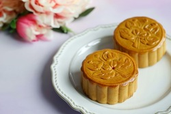 Celebrate Mooncake festival with traditional mooncakes on vintage plate over pastel purple background with blurred peony flowers. Holidays food and dessert theme Chinese Mid-Autumn Festival.