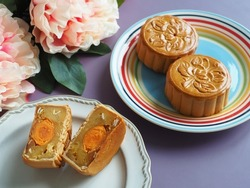 Celebrate Mooncake festival with traditional mooncakes on vintage plates over pastel purple background with blurred peony flowers. Holidays food and dessert theme Chinese Mid-Autumn Festival.