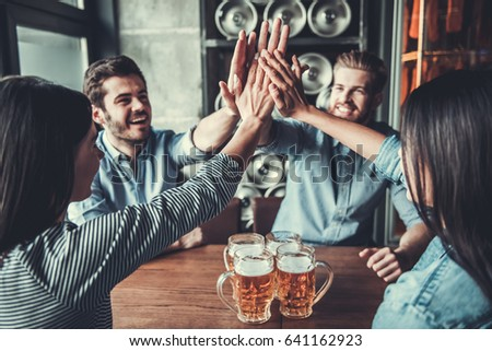 Celebrate success together. Happy young friends drinking beer and giving high five gesture at pub. #641162923