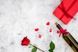 Celebrate Valentine's day. Wine, glasses, red rose, heart sign, gift box on grey background top view copy space