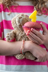 Celebrating a girl's fourth birthday, a girl in a pink and white shirt holding a small teddy bear and a pink cupcake with a candle with the number four, close-up