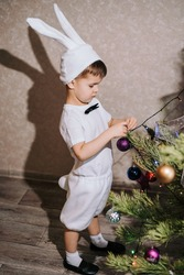 Celebrating Christmas. A cute baby in a bunny or rabbit costume decorates the Christmas tree with New Year's toys.
