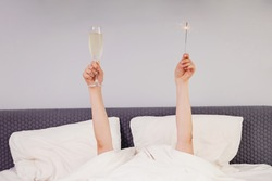 Celebrating Christmas or New year Alone. Hands holding glass of sparkling wine and sparkler while lying in bed.