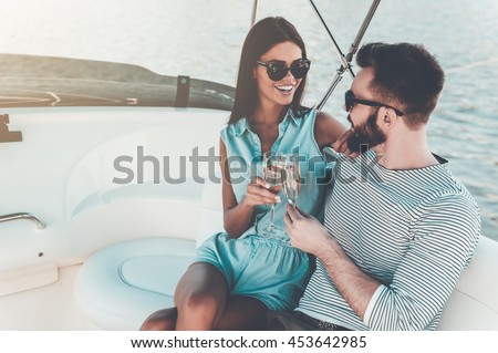 Celebrating love. Smiling young couple holding glasses with champagne and looking at each other while sitting on the board of yacht