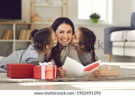 Celebrating Mothers day or Womans day at home concept. Happy young mother woman lying on floor between kissing her daughters and reading handmade postcard for mom on holiday