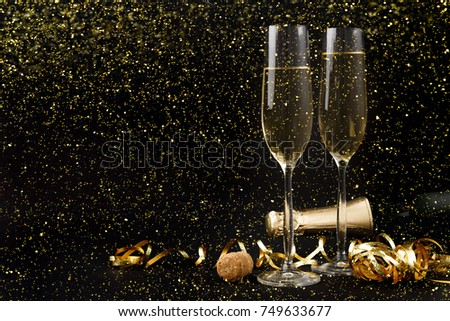 Celebrating new year, birthday, xmas party. Bottle of champagne, flutes and colorful tinsel on black backgroud with golden glitters, copy space. Mockup for postcard #749633677