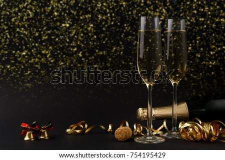 Celebrating new year, birthday, xmas party. Bottle of champagne, flutes and colorful tinsel on black backgroud with golden glitters, copy space. Mockup for postcard #754195429