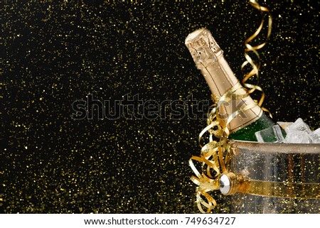 Celebrating new year, birthday, xmas party. Bottle of champagne in a bucket and colorful tinsel on black backgroud with golden glitters, copy space. Mockup for postcard #749634727
