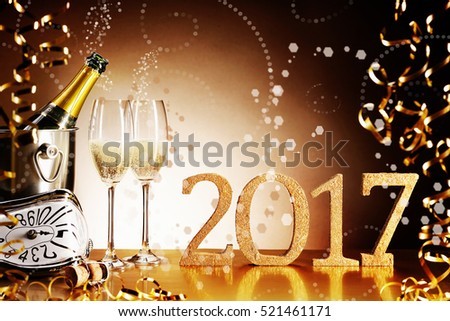 Celebrating 2017 New Years Eve with a festive still life of sparkling champagne with escaping bubbles, gold party streamers and a glittering golden date for a luxury holiday background with copy space