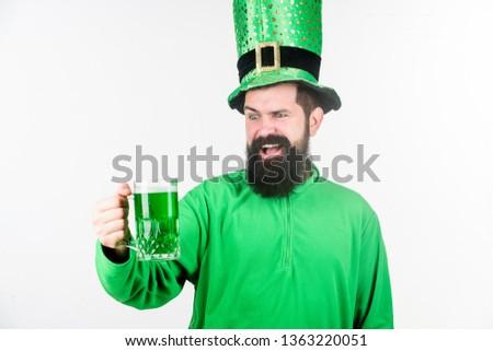 Celebrating saint patricks day in bar. Hipster in leprechaun hat holding beer mug. Bearded man toasting to saint patricks day. Irish man with beard drinking green beer. I dont get drunk I get awesome.
