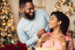 Celebrating Special Day. Smiling black man wearing jewel necklace on his happy young woman. Beautiful african american family spending time together in luxury cafe, having romantic dinner