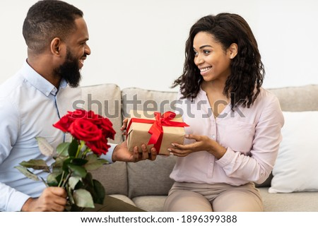 Celebrating Special Occasion. Portrait of smiling african american guy giving his girlfriend wrapped box with present and a bouquet of red roses. Happy man greeting lady with international women's day