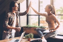 Celebrating success. Cheerful young man and woman giving high-five while having coffee break in creative office