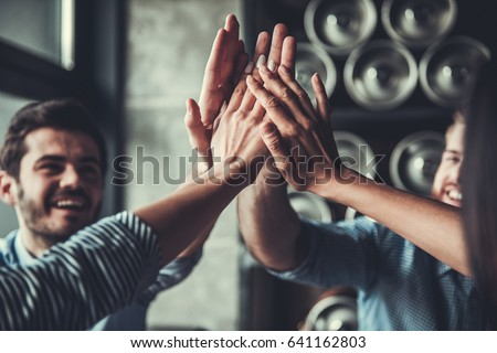 Celebrating success. Cropped image of handsome young business people celebrating success and making high five gesture in pub.