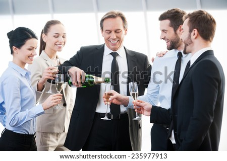Celebrating success. Group of business people holding flutes with champagne and smiling while standing close to each other indoors