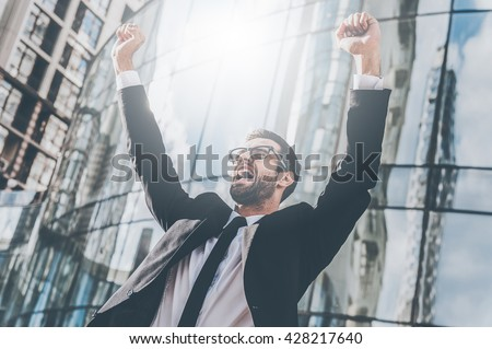 Celebrating success. Low angle view of excited young businessman keeping arms raised and expressing positivity while standing outdoors with office building in the background